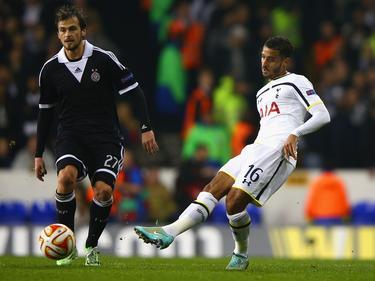 Danko Lazović (l.) van Partizan kijkt toe hoe Kyle Naughton (r.) van Tottenham Hotspur de bal speelt tijdens de Europa League wedstrijd. (27-11-2014)