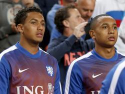 Jaïro Riedewald (l.) en Kenny Tete zijn tegenwoordig basisspeler bij Ajax, maar tijdens de kwalificatiewedstrijd van Oranje in de Amsterdam ArenA zijn de jongelingen wisselspeler. Hier kijken ze samen toe tijdens het duel. (03-09-2015)