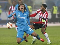 Georginio Wijnaldum (r.) van PSV zet een harde tackle in op Zenit St. Petersburg-speler Axel Witsel in de zestiende finale van de Europa League. (26-02-2015)