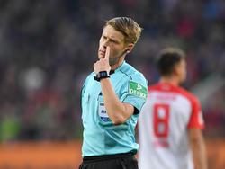Schiedsrichter Christian Dingert fällt nach einer strittigen Szene eine Entscheidung