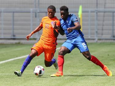 Kenneth Paal (l.) in duel met de Fransman Faitout Maouassa (r.) tijdens het EK U19 in Duitsland. (18-07-2016)