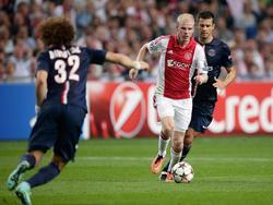 Davy Klaassen (m.) aan de bal, terwijl David Luiz (l.) aan komt stormen. Thiago Motta (r.) kan niet meer bij de bal. (17-09-2014)