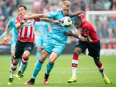 Nicolai Jørgensen (m.) houdt zich tijdens de wedstrijd PSV - Feyenoord staande tussen Andrés Guardado en Nicolas Isimat-Mirin. (18-09-2016)