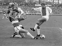 Piet Keizer (r.) haalt uit, maar ziet zijn schot geblokt worden tegen Holland Sport. Klaas Nuninga kijkt op de achtergrond toe. (02-05-1971)