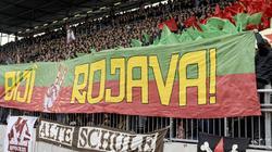 """Fans von St. Pauli halten ein Banner mit dem Schriftzug """"Biji Rojava"""" (""""Es lebe Rojava"""") in die Höhe"""