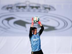Courtois atrapa el cuero con la camiseta del Madrid.