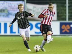 Merlin Schütte (l.) probeert tevergeefs Jordy de Wijs te achterhalen tijdens Jong PSV - Jong FC Twente. (26-01-2015).