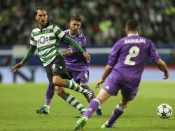 Sporting CP-spits Bas Dost (r.) kaatst de bal terug terwijl hij onder druk wordt gezet door Real Madrid-verdediger Sergio Ramos (m.). (22-11-2016)