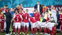 Dänemarks Spieler stehen schockiert am Ort des Geschehens
