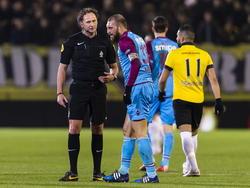 Scheidsrechter Reinold Wiedemijer (l.) praat met Vitesse-aanvoerder Guram Kashia (m.), die pijn heeft na een overtreding. (07-02-2015)