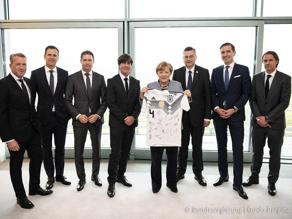 Bundeskanzlerin Angela Merkel (M) erhält WM-Trikot der deutsche Mannschaft. (Bildquelle: twitter.com/dfb_praesident)