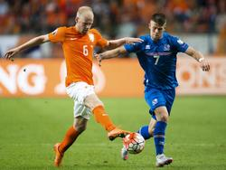 Davy Klaassen (l.) probeert Jóhann Guðmundsson (r.) uit te kappen tijdens de EK-kwalificatiewedstrijd tussen Nederland en IJsland.