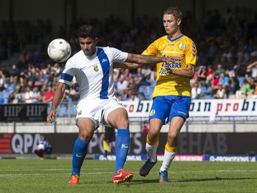 Jonathan Reis (l.) schermt namens Vitesse de bal af. Ingo van Weert (r.) van RKC Waalwijk kijkt toe. (11-08-2013)