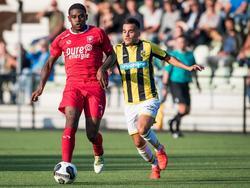 Kyle Ebecilio (l.) kijkt vooruit met de bal aan de voet, maar Anıl Mercan (r.) maakt zich klaar voor de onderschepping tijdens Jong Vitesse - Jong FC Twente. (22-08-2016)