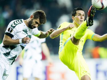 Selim Ay (l.) trekt zijn hoofd in als Jérémy Perbet (r.) zijn been uitstrekt om bij de bal te komen. (08-12-2016)