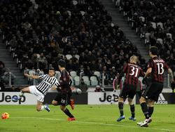 Stefano Sturaro (l.) doet zijn uiterste best om bij een lage voorzet te komen, terwijl spelers van AC Milan toekijken. (21-11-2015)