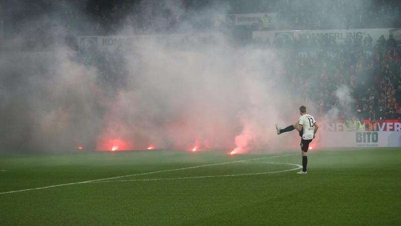 Dichte Rauchschwaden durchziehen das Mainzer Stadion, nachdem Feuerwerkskörper aus dem Gästeblock auf dem Rasen gelandet sind
