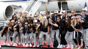 Die US-Fußballerinnen präsentieren bei der Ankunft in New York den WM-Pokal