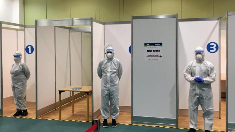 Helfer stehen in einem Corona-Testzentrum der IBU für Tests im Rahmen des Hygiene-Konzepts bereit