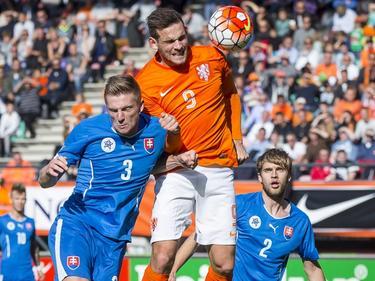 Vincent Janssen (m.) wint het kopduel van Milan Škriniar (l.) tijdens de EK-kwalificatiewedstrijd tussen Jong Oranje en Jong Slowakije. (11-10-2015)