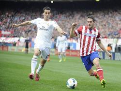 Álvaro Arbeloa (l.) en Koke (r.) in een pittig gevecht om de bal. (2-3-2014)