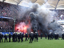 Feuerwerkskörper brennen vor dem Abpfiff auf der Tribüne, während Polizisten auf dem Spielfeld stehen