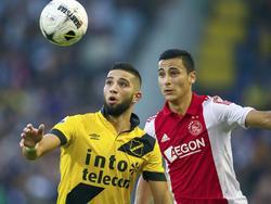 Anwar El Ghazi (r.) en Adnane Tighadouini staren na de bal tijdens het competitieduel NAC Breda - Ajax. (27-09-2014)