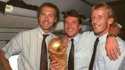 Heimflug mit Pokal: Teamchef Franz Beckenbauer (l.), Lothar Matthäus (M.) und Andreas Brehme feiern den WM-Sieg 1990