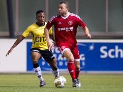 Elson Hooi (l.) zet vol druk op Travis Brent, die daardoor snel moet handelen tijdens de competitiewedstrijd Almere City - NAC Breda. (18-12-2015)