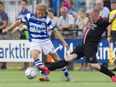 Thijs Bouma (l.) ontwijkt handig een sliding van Patrick van Haren (r.) tijdens een oefenwedstrijd van De Graafschap tegen VIOD. (04-07-2015)