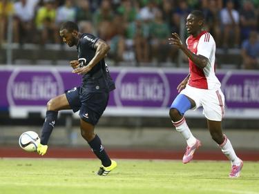 Yaya Sanogo (r.) zet de achtervolging in tijdens de laatste oefenwedstrijd van Ajax, op Franse bodem tegen AS Saint-Étienne. Kévin Théophile-Catherine moet snel handelen. (22-07-2015)