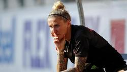 Anja Mittag sitzt während eines Fußballspiels auf der Bank