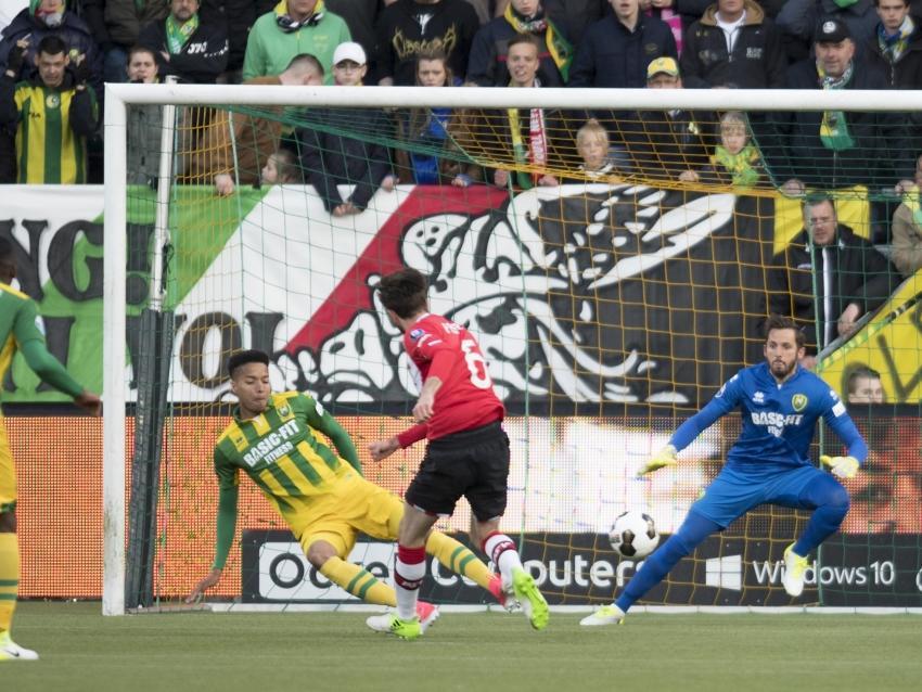 Davy Pröpper schiet op doel van ADO Den Haag en scoort. Tyronne Ebuehi (l.) is te laat om de bal te blokken, terwijl ook Robert Zwinkels (r.) niet kan redden.