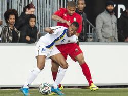 Curuçao en Suriname spelen een oefenduel in Almere. Jeremy de Nooijer (l.) schermt hier de bal af van Milano Koenders (r.). (21-05-2015)