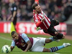 Leandro Bacuna (l.) laat Steven Fletcher vliegen tijdens de competitiewedstrijd tussen Aston Villa en Sunderland. (14-03-2015)