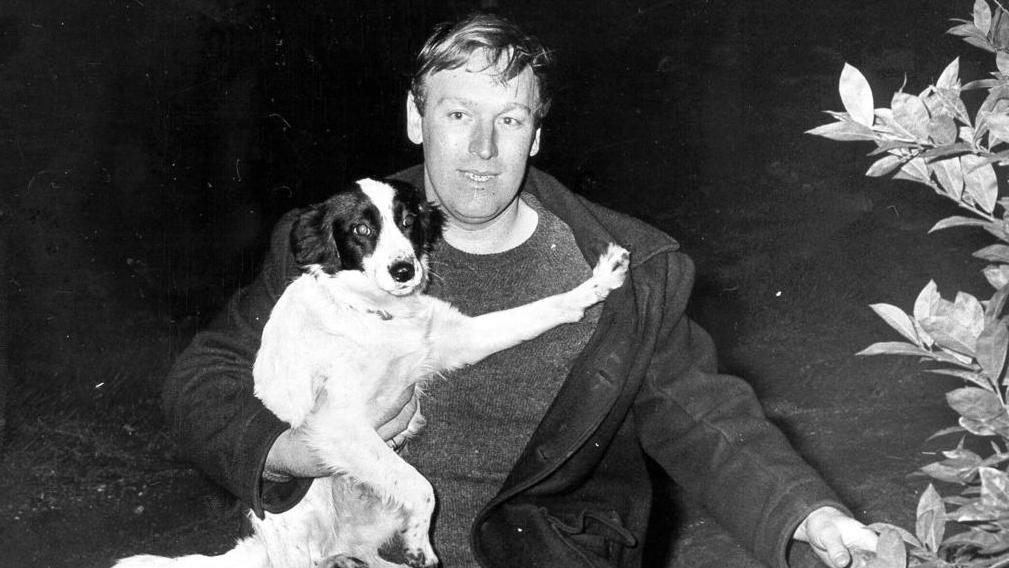 David Corbett mit seinem Hund Pickles neben dem Busch, unter dem der WM-Pokal lag