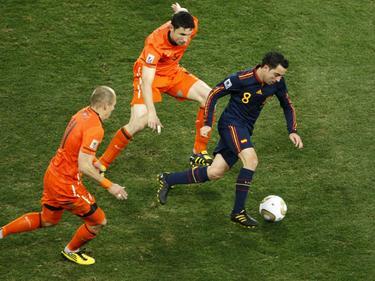 Xavi Hérnandez (r.) dribbelt voorbij Arjen Robben (l.) en Mark van Bommel (m.). De Spanjaard houdt de bal dicht bij zich. (06-07-2010)