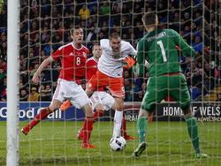 Bas Dost (m.) krijgt veel vrijheid bij de tweede paal na een voorzet en de spits kopt raak voor zijn eerste goal in het shirt van het Nederlands elftal. Wayne Hennessey (r.) wordt verschalkt, Nederland komt op een 0-1 voorsprong. (13-11-2015)