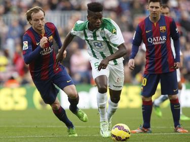 Patrick Ekeng van Córdoba snelt voorbij Ivan Rakitić. Lionel Messi kijkt op de achtergrond toe. (20-12-2014)