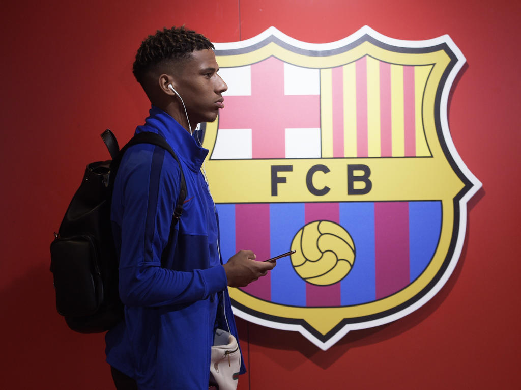 Todibo pasa por delante del escudo del Barça en el Camp Nou.