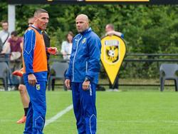 Een deel van de trainersstaf overlegt op de training van Vitesse. Hier praten Peter Bosz (r.) en Hendrie Krüzen.
