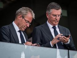Algemeen directeur Eric Gudde (l.) en technisch directeur Martin val Geel (r.) kijken tijdens PSV - Feyenoord even op hun telefoon. (30-08-2015)