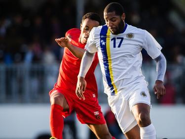 Kemy Agustien (r.) vecht een duel uit met Roland Alberg tijdens de oefeninterland tussen Suriname en Curaçao. (19-05-2015)