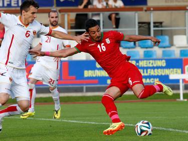 Reza Ghoochannejhad (r.) beschermt de bal tegen Zarko Tomasevic (l.). (30-5-2014)