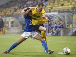 Derwin Martina (l.) kan niet tot na de wedstrijd wachten om het shirtje van Marc Höcher (r.) in ontvangst te nemen. De twee degradanten spelen tegen elkaar tijdens de seizoensouverture van de Jupiler League. (08-08-2014)