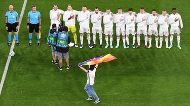 Ein junger Mann rannte mit einer Regenbogenfahne über das Spielfeld