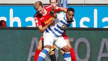 Duisburgs Joseph-Claude Gyau schirmt den Ball gegen Jahn-Profi Marco Güttner ab