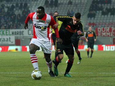 Kelvin Maynard (l.) is niet onder de indruk van Deniz Türüç (r.), die druk probeert te zetten op de verdediger van FC Emmen. (08-03-2013)