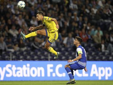 Eran Zahavy (l.) springt heel hoog en wint daardoor het duel van Rúben Neves (r.) tijdens de Champions League-ontmoeting tussen FC Porto en Maccabi Tel Aviv. (20-10-2015)