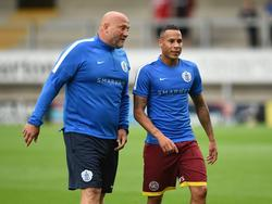 Assistent-trainer Dirk Heesen (l.) is in gesprek met Tjaronn Chery (r.) tijdens een training van Queens Park Rangers (26-07-2016).